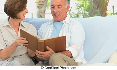Senior couple looking at a book on the sofa