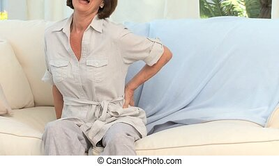 Retired woman with a back pain in her living room