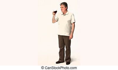 Senior man trying a glass of wine against a white background