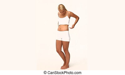 Blond woman measuring her stomach isolated on a white...