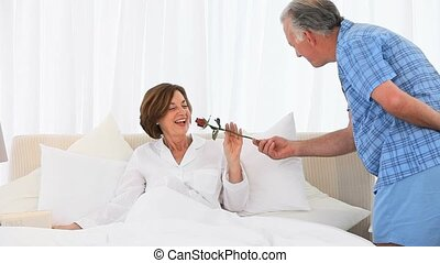 Senior man offering a rose to his wife in the bedroom