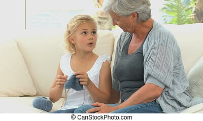 A little girl learning to knit with her Grandmother on a...