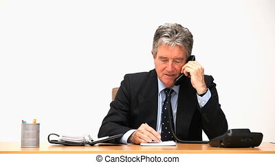Elderly businessman making a phone call at his desk