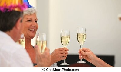 Retired friends drinking champagne in the dinning room