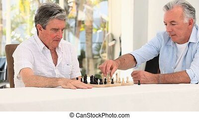 Senior friends men playing chess in a nursing home