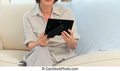Retired woman looking at a photo on the sofa