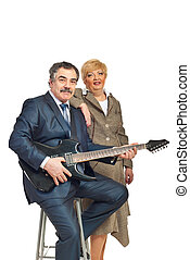 Mature couple playing guitar - Mature business man in formal...