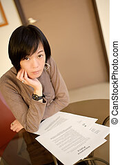 insurance policy - Asian woman reading insurance policy...