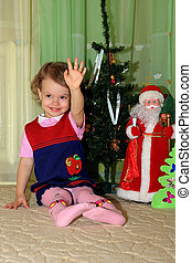 Girl sits under conifer. - A little girl sits under a...