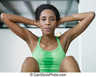 african woman doing series of crunch in gym - young african...