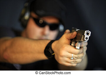 Pistol - Man pointing a gun looking at the camera