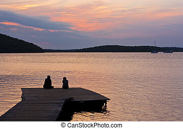 Couple on pier with sunset - Man and woman on pier with...