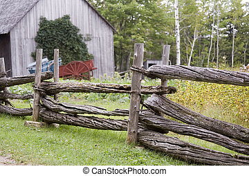 Cedar Fence - Wooden fence in front of barn in a rural area