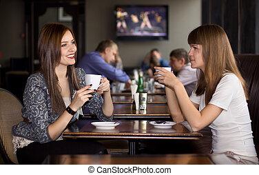 two girlfriens talking in cafe