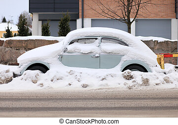 Car Covered by Snow - Side View - light blue car in a street...