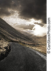 Rugged landscape with roadway - Winding road leading through...