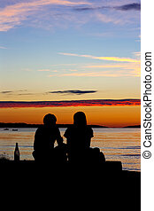 Young couple with alcohol on beach - Silhouette of young...