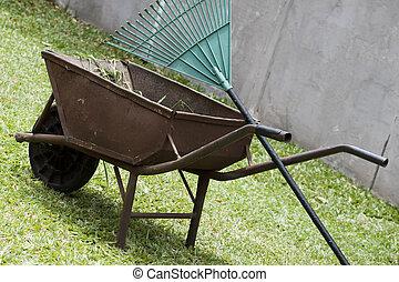 wheelbarrow and rake in the garden