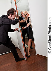 Businessman pushing the door to prevent people entering room
