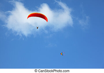 The red parachute flies in the blue sky - The operated red...