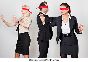 Group of disoriented businesspeople with red ribbons on eyes