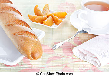 Baguette on plate, peach dessert and a cup of tea