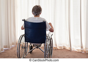 Mature woman in her wheelchair with her back to the camera...