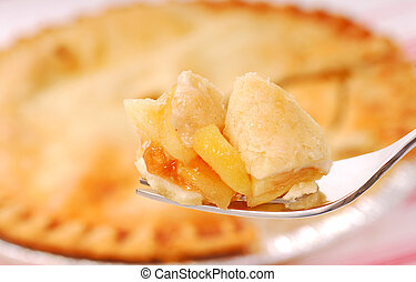Bite of apple pie on a fork