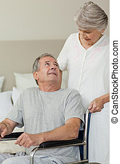 Retired man in his wheelchair with his wife