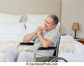 Smiling senior man in his wheelchair  at home