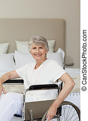 Smiling senior woman in her wheelchair at home