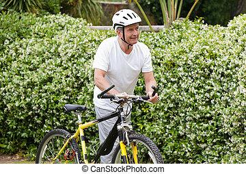Mature man walking with his mountain bike