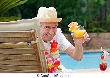Mature man drinking a cocktail  beside the swimming pool