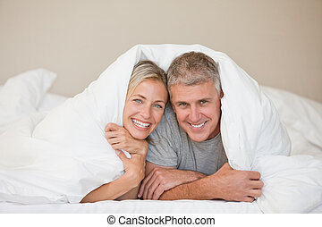 Couple lying down in their bed at home