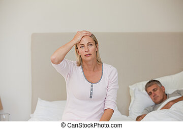 Woman having a headache while her husband is sleeping