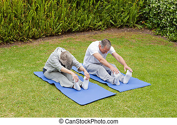 Senior couple doing their streches in the garden