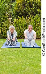 Senior couple doing their streches in the garden
