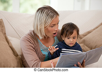 Mother looking at a book with her son at home