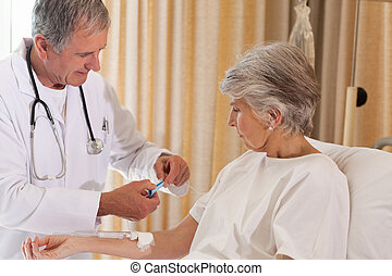 Doctor putting a drip on the arm of his patient