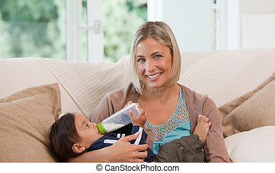 Mother giving a  bottle of milk to her son