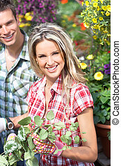 Gardening. Young smiling people florists working in the...