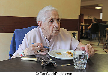 senior woman eating - senior woman smiling and eating in a...