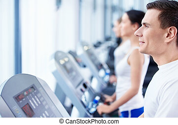 Fitness - Happy young people on treadmills