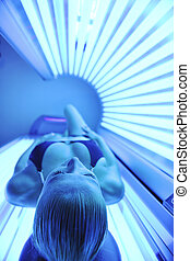 beauty and spa solarium treatment - young woman at laying on...