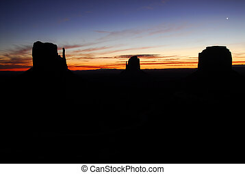 """Silhouette of the """"Mittens"""" in Monument Valley at dawn"""