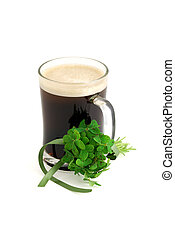 Dark beer in glass and bouquet of false shamrock Oxalis with...