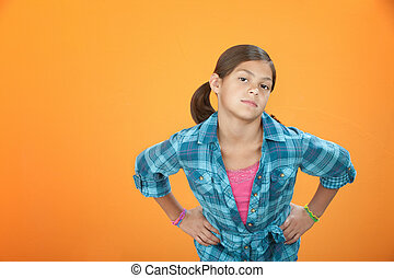 Kid Attitude - Young girl on orange background with hands on...