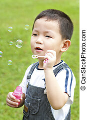 Blowing bubbles - Asian boy blowing bubbles outdoor