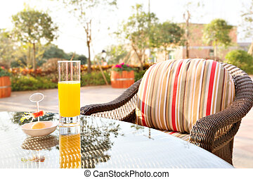 orange juice and ice cream on table in a garden.
