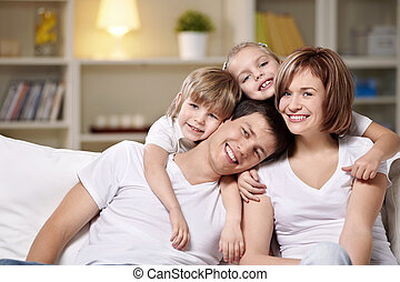 Laughing families with children at home in the evening